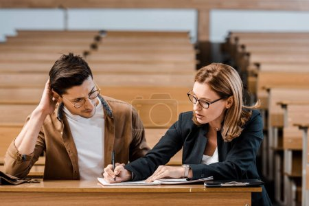 female teacher checking exam results of male student in classroom