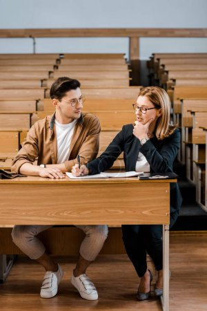 pensive female teacher touching chin and checking exam results of male student in classroom
