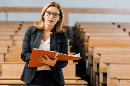 female university professor holding journal and looking at camera in classroom