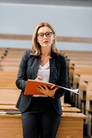 female university professor looking at camera, holding journal and writing in classroom