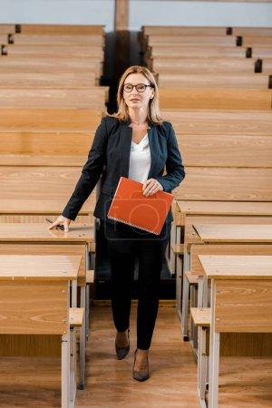 female university professor in formal wear holding journal and pen in classroom