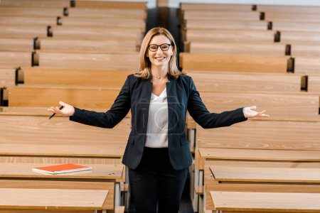 happy female university professor with outstretched hands looking at camera in classroom