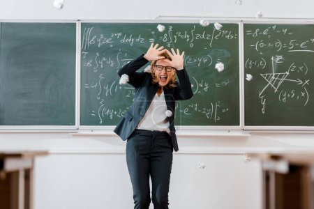 crumpled paper balls flying at frightened female teacher in classroom with chalkboard on background