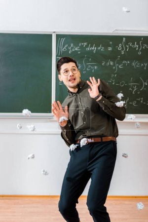 crumpled paper balls flying at frightened male teacher in classroom with chalkboard on background