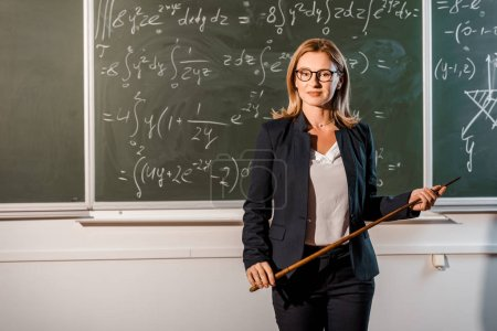 attractive female teacher with wooden pointer explaining mathematical equations in classroom