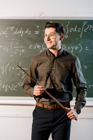 smiling male teacher in formal wear holding wooden pointer in front of chalkboard with equations