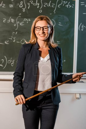 female teacher in formal wear with wooden pointer explaining mathematical equations in classroom
