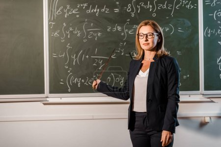 beautiful female teacher with wooden pointer explaining mathematical equations in classroom