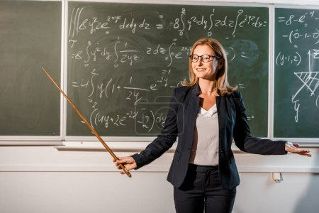smiling female teacher with wooden pointer explaining mathematical equations in classroom
