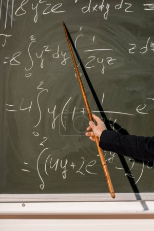 cropped view of female teacher with wooden pointer explaining mathematical equations in classroom