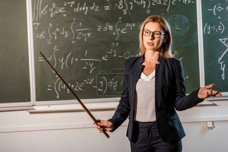 Photo pour Enseignante en tenue formelle avec pointeur en bois expliquant les équations mathématiques en classe - image libre de droit