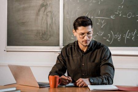 cher professeur masculin dans des lunettes assis au bureau de l'ordinateur avec des ordinateurs portables et café dans la salle de classe
