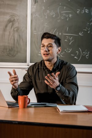 male teacher in glasses sitting at desk and explaining equations in maths classroom
