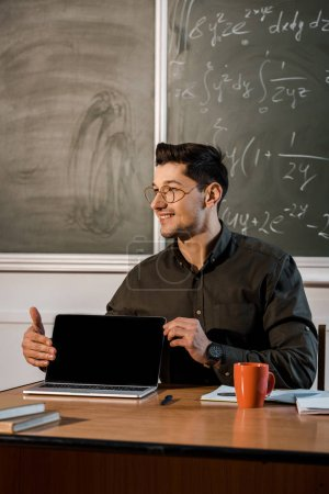 Photo for Smiling male teacher in glasses sitting at desk and showing laptop with blank screen in classroom - Royalty Free Image