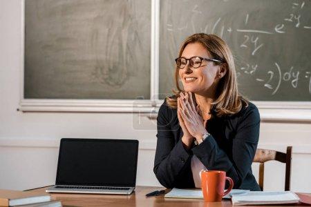 Photo pour Assis à l'ordinateur de bureau avec écran blanc dans la salle de classe souriant enseignante - image libre de droit