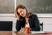 tired female teacher with eyes closed sitting at computer desk in classroom