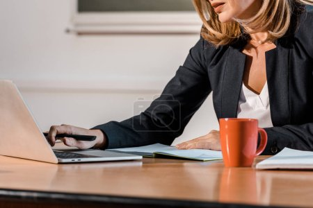 cropped view of teacher using laptop and sitting at desk