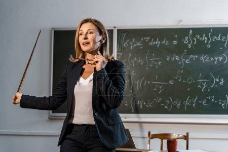 Photo pour Enseignante avec pointeur en bois tenant des lunettes et expliquant les équations mathématiques en salle de classe - image libre de droit