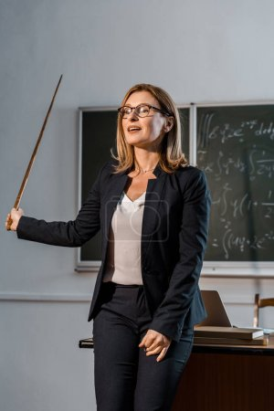 female teacher with wooden pointer explaining mathematical equations in classroom