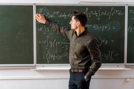 male teacher in formal wear wiping mathematical equations with sponge in classroom