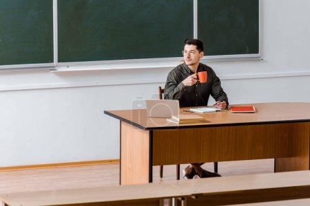 Photo pour Enseignant de sexe masculin assis au bureau de l'ordinateur et de boire du café dans la salle de classe - image libre de droit