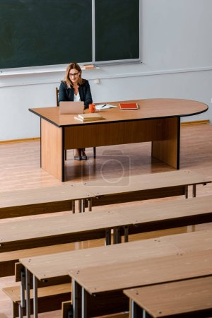 Photo for Female university professor sitting at desk and using laptop in classroom - Royalty Free Image