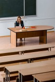 female university professor sitting at desk and using laptop in classroom