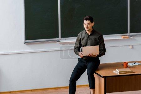 Foto de Profesor en desgaste formal sentado en el escritorio y mantener laptop en aula - Imagen libre de derechos