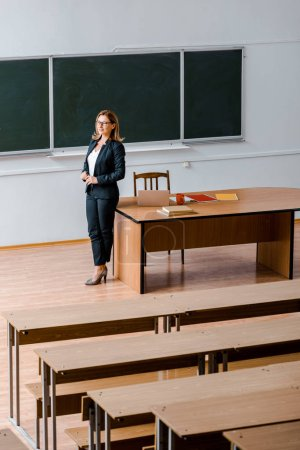 female university professor in formal wear standing near chalkboard in classroom
