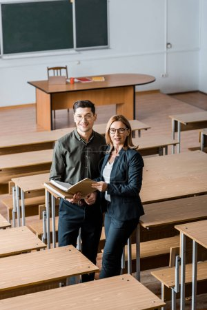 Photo for Male student and female teacher holding university books and looking at camera in classroom - Royalty Free Image