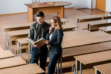Foto de Sonriente hombre estudiante y maestra en Universidad libros en aula - Imagen libre de derechos