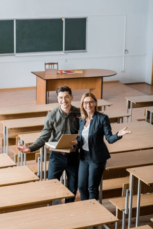 happy male student and female teacher with outstretched hands holding university books in classroom
