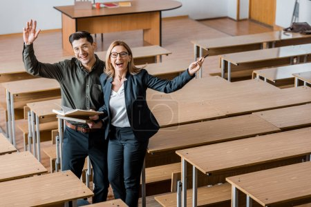 Photo for Cheerful male student and female teacher with outstretched hands holding university books in classroom - Royalty Free Image