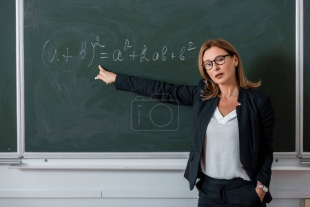 female teacher looking at camera and pointing with finger at mathematical equation on chalkboard in class