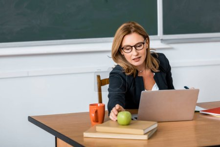 beautiful female teacher in glasses sitting at computer desk and reaching for apple in classroom