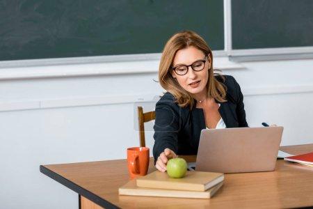 Photo pour Belle institutrice dans les verres, assis au bureau de l'ordinateur et atteignant pour apple en salle de classe - image libre de droit