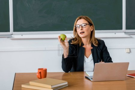 female teacher sitting at computer desk and holding apple in classroom