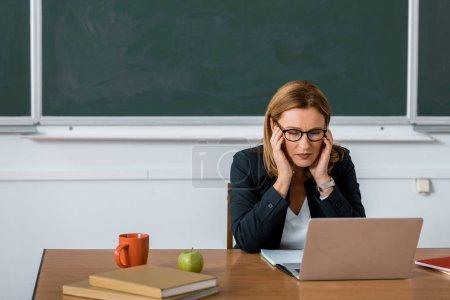 Photo pour Enseignante, assis au bureau de l'ordinateur et avoir des maux de tête en classe - image libre de droit
