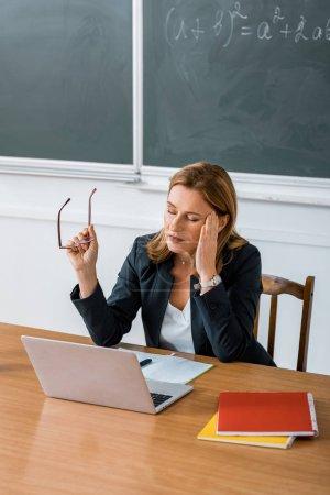 Photo pour Enseignante, assis au bureau de l'ordinateur, tenant des lunettes et avoir des maux de tête en classe - image libre de droit
