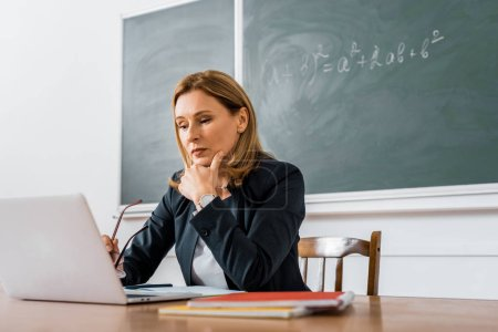Photo pour Enseignante assise au bureau et utilisant un ordinateur pendant les cours en classe - image libre de droit