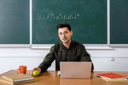 male teacher in glasses sitting at computer desk, holding apple and looking at camera in classroom