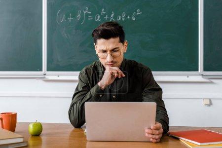 Photo pour Enseignant de sexe masculin songeur dans des verres, assis au bureau et utilisez l'ordinateur dans la salle de classe - image libre de droit