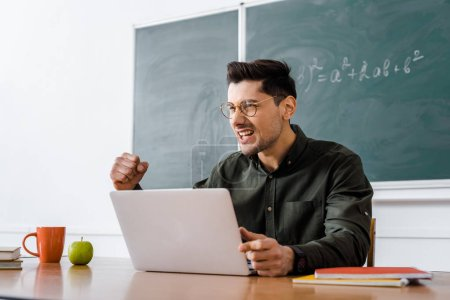 excited male teacher sitting at desk and using laptop in classroom
