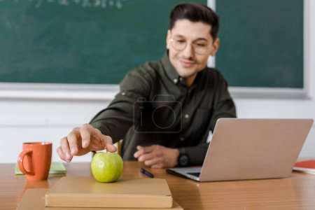 male teacher in glasses sitting at computer desk and reaching for apple in classroom