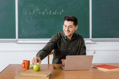 Photo pour Professeur mâle souriant dans des lunettes assis au bureau de l'ordinateur et tendre la main pour pomme dans la salle de classe - image libre de droit