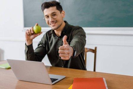 Photo pour Souriant enseignant de sexe masculin dans les verres, tenant la pomme et montrant le pouce en haut signe au bureau d'ordinateur en salle de classe - image libre de droit