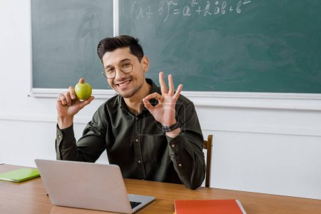 smiling male teacher in glasses holding apple and showing ok sign at computer desk in classroom