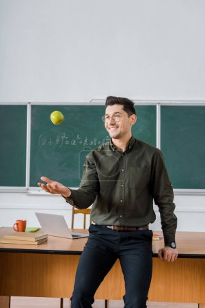 smiling male teacher throwing apple in class with chalkboard and desk on background