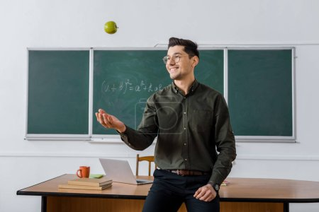 happy male teacher throwing apple in classroom