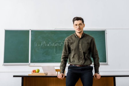 Photo for Serious male teacher in formal wear looking at camera and standing near desk in classroom - Royalty Free Image
